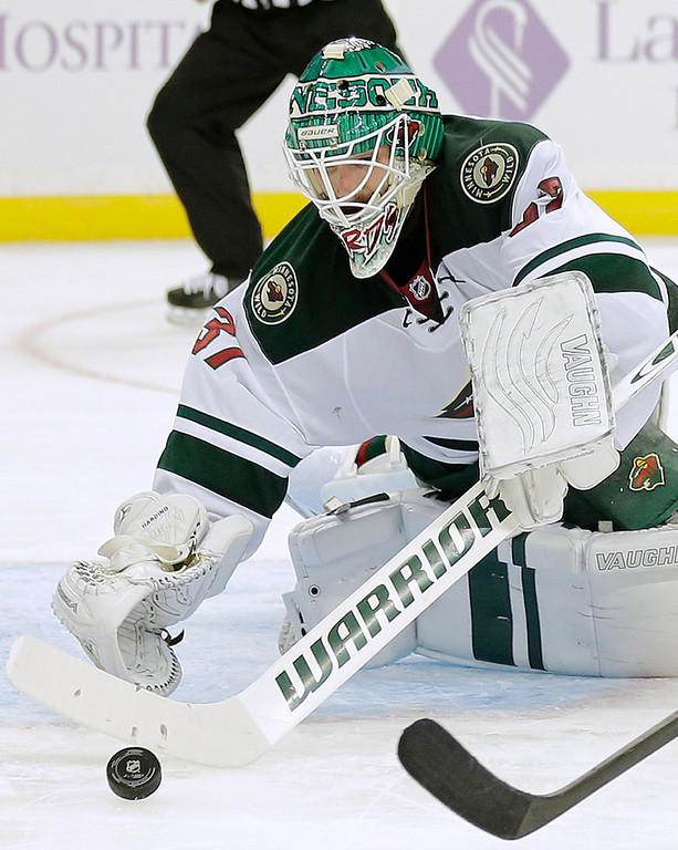 . Minnesota Wild goalie Josh Harding dives on a loose puck after making a save on a shot by the Tampa Bay Lightning during the second period.  (AP Photo/Chris O\'Meara)