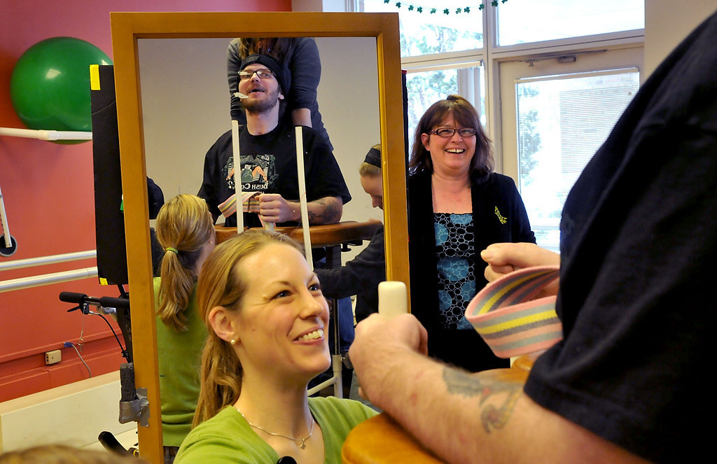 . Physical therapist Lena Haugland, left, and Zack Mohs� mother, Cheryl Young of South St. Paul, encourage Mohs as he works on his movement in a large therapeutic walker. (Pioneer Press: John Doman)
