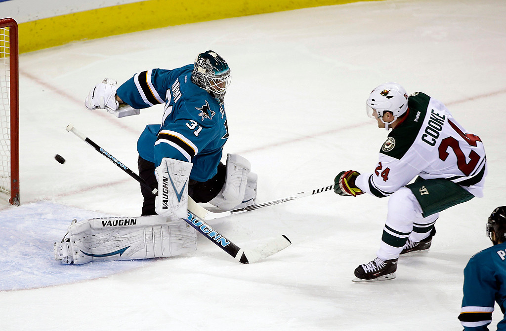 . Minnesota Wild\'s Matt Cooke (24) scores past San Jose Sharks goalie Antti Niemi, of Finland, during the first period of an NHL hockey game on Saturday, Jan. 25, 2014, in San Jose, Calif. (AP Photo/Marcio Jose Sanchez)