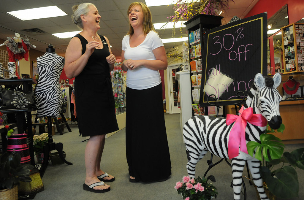 """. Glenette Sperry, left, and her daughter Tanika Bender, store owners of Floral Creations in Lindstrom, Minnesota, talk about how the colors and theme in their store is similar to the chair \""""Petals & Stripes\"""" out front Friday July 26, 2013. (Pioneer Press: Jean Pieri)"""