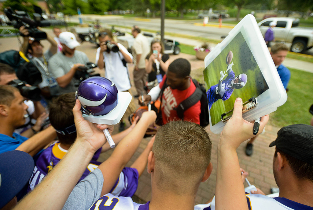 . Fans hold tight to their wares as they wait for an autograph from Vikings wide receiver and ex-Packer Greg Jennings at training camp.  (Pioneer Press: Ben Garvin)