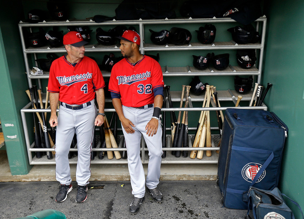 . Minnesota Twins coach Paul Molitor (4) and center fielder Aaron Hicks (32) talk before an exhibition baseball game in Fort Myers, Fla., Saturday, March 29, 2014. (AP Photo/Gerald Herbert)