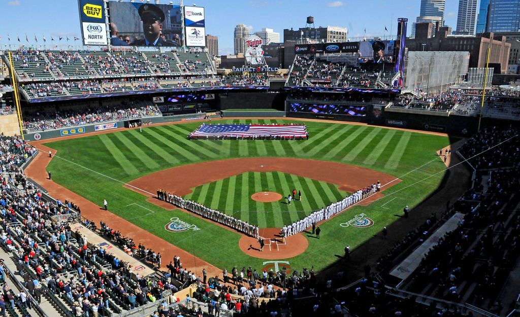 . Players line up as a large American flag is displayed in the outfield during the singing of National Anthem before the start of Monday\'s home opener at Target Field. (Pioneer Press: John Autey)