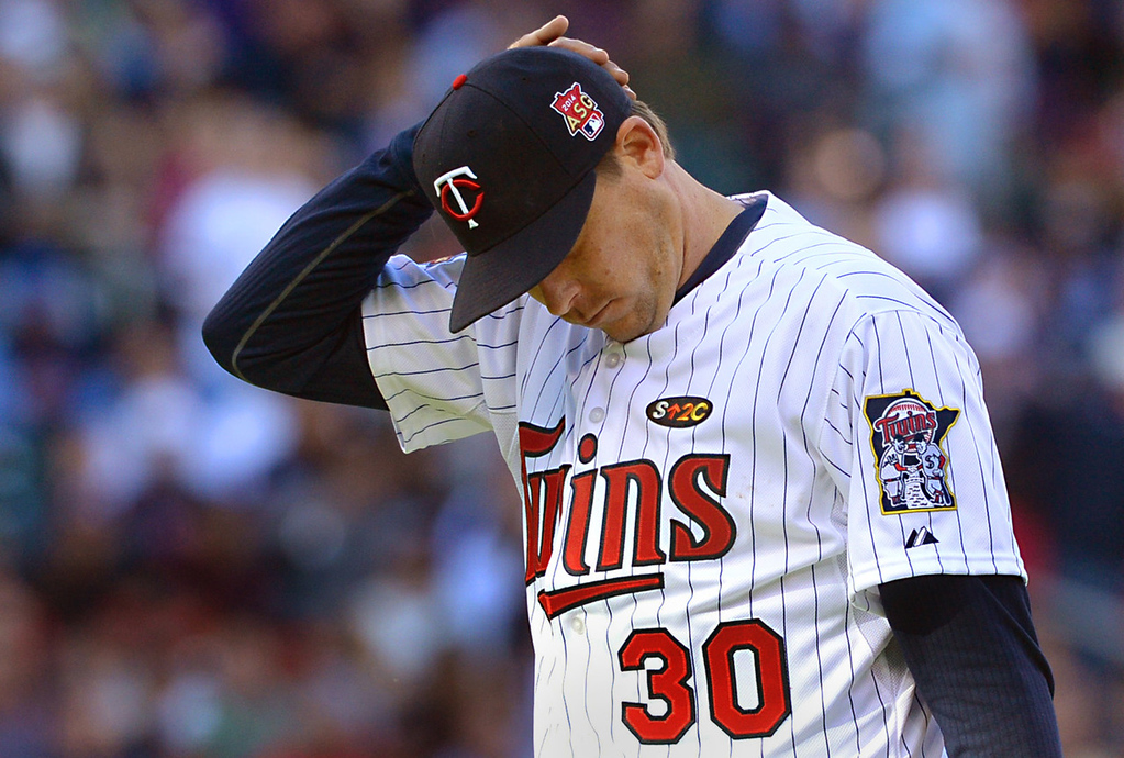 . Minnesota starting pitcher Kevin Correia walks back to the dugout after getting yanked by manager Ron Gardenhire with two outs in the fifth inning. Correia gave up six earned runs on nine hits in the loss to Oakland. (Pioneer Press: John Autey)