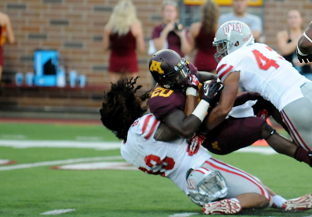 . UNLV\'s Sonny Sanitoa loses his helmet as he tackles Minnesota running back Donnell Kirkwood during the second quarter.  (Pioneer Press: John Autey)