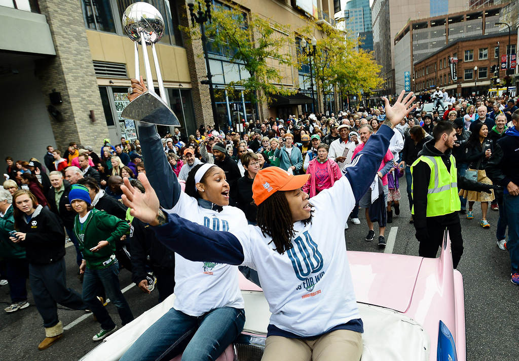 . Minnesota Lynx star Maya Moore, left, hoists the WNBA championship trophy as she and teammate Seimone Augustus soak up the love during a victory parade along Nicollet Avenue in Minneapolis on Monday, October 14, 2013. (Pioneer Press: Ben Garvin)