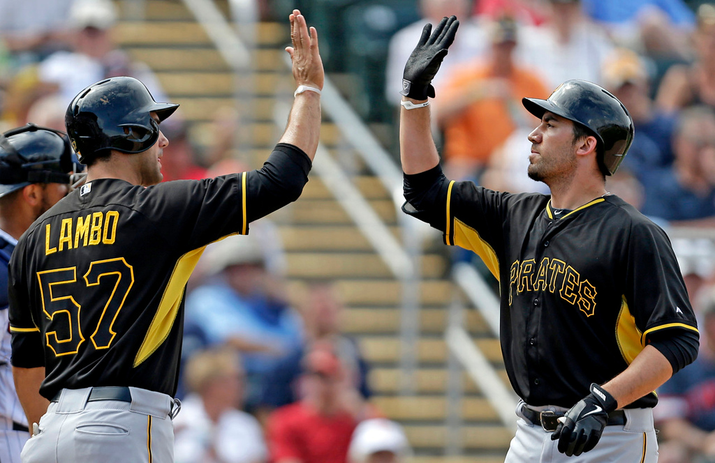 . Pirates first baseman Travis Ishikawa, right, is greeted by teammate Andrew Lambo after the two scored on Ishikawa\'s two-run homer over the center field wall in the sixth inning against the Twins. (AP Photo/Gerald Herbert)