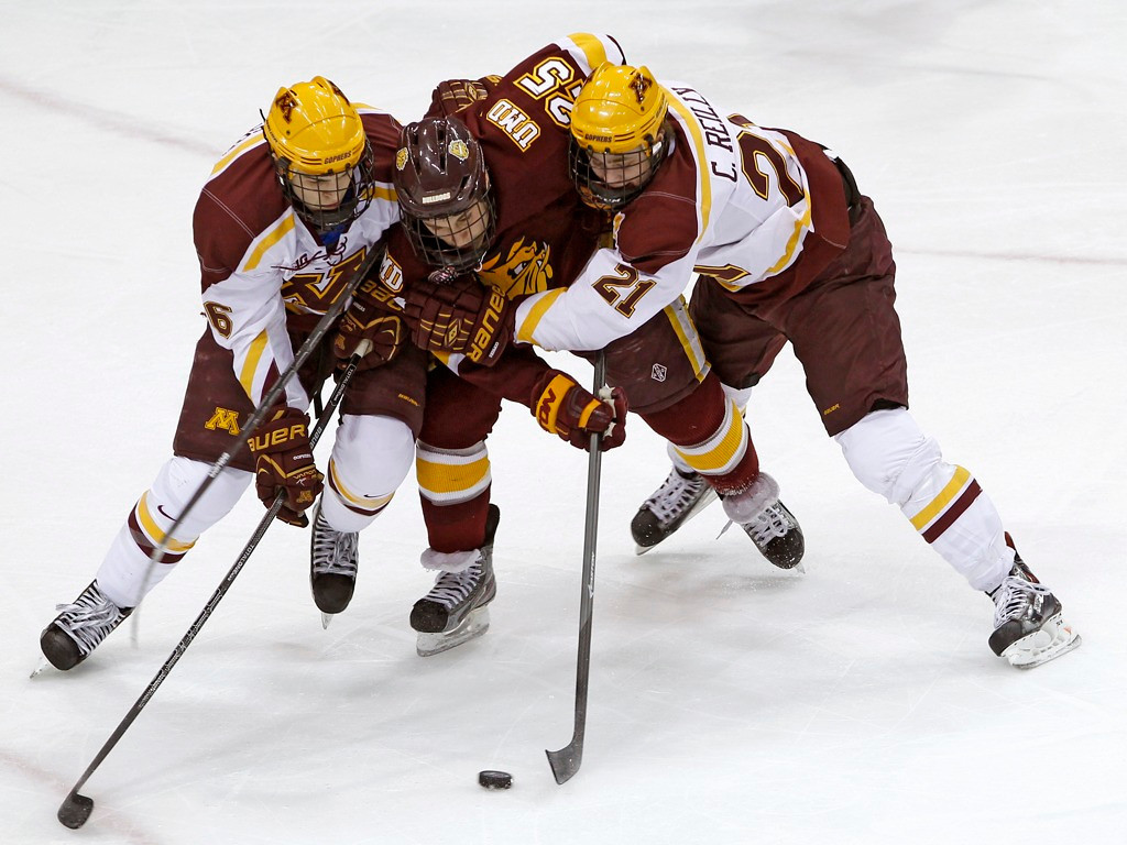 . Bulldogs winger Justin Crandall, center, is squeezed between Minnesota\'s Christian Isackson, left, and Connor Reilly as they pursue the puck during the first period. (AP Photo/Ann Heisenfelt)