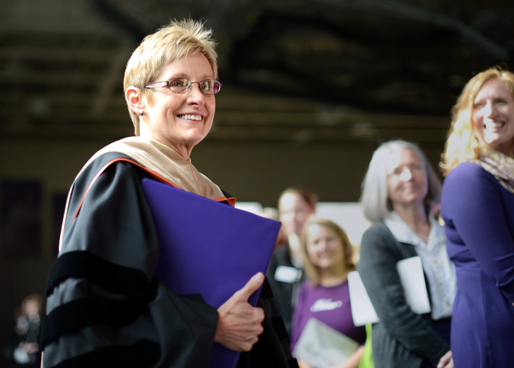 . Dr. Julie Sullivan smiles and is greeted by warm applause as she walks toward the stage to be inaugurated as the new president of the University of St. Thomas at the Anderson Athletic and Recreation Complex in St. Paul on Thursday, October 17, 2013. Sullivan is the first woman and first lay person to lead the Catholic university after 127 years of priests at the helm. (Pioneer Press: Chris Polydoroff)