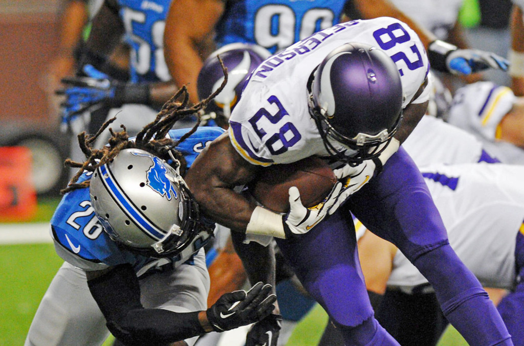 . Vikings running back Adrian Peterson crosses the goal line on a four-yard touchdown run, one of his three touchdowns, while colliding with Lions free safety Louis Delmas in the second quarter.  (Pioneer Press: Chris Polydoroff)