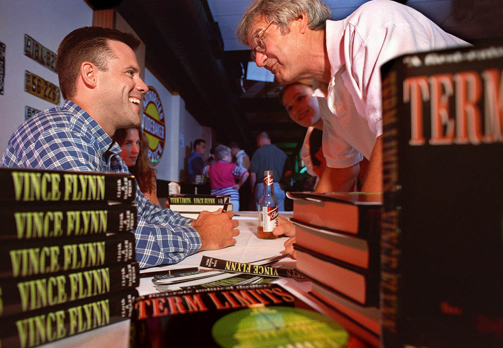 . Flynn, left,  signs a copy of his book for Gus Metzger of St. Paul during an autographing party at O\'Gara\'s in St. Paul in 1999. Metzger read the techno-thriller at his cabin over a weekend and ordered 40 copies to give to friends. (Pioneer Press file)