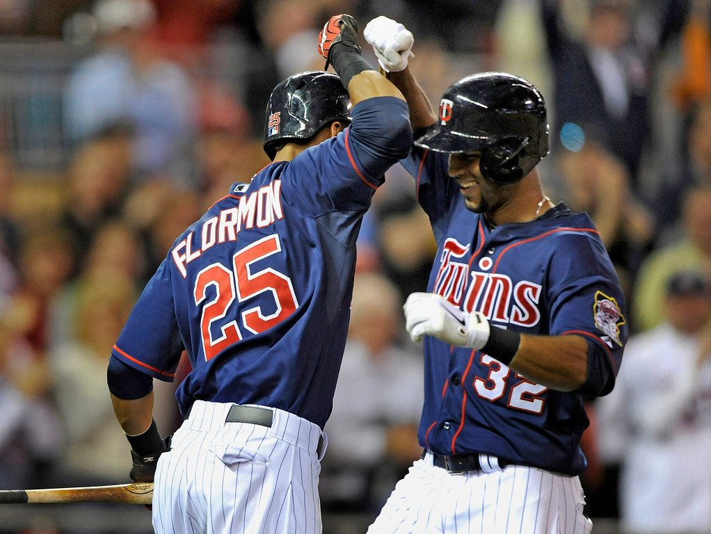 . Minnesota\'s Pedro Florimon, left, congratulates teammate Aaron Hicks on a solo home run, his second of the game, during the the sixth inning of the Twins\' 10-3 win over the Chicago White Sox at Target Field in Minneapolis on Monday May 13, 2013. (Photo by Hannah Foslien/Getty Images)
