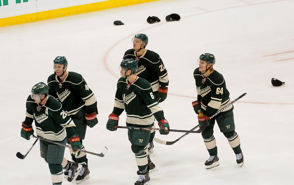 . Minnesota Wild  Ryan Suter, bottom left, leads his team back towards the bench as fans throw hats onto the ice after his hat trick.(Pioneer Press: Sherri LaRose-Chiglo)