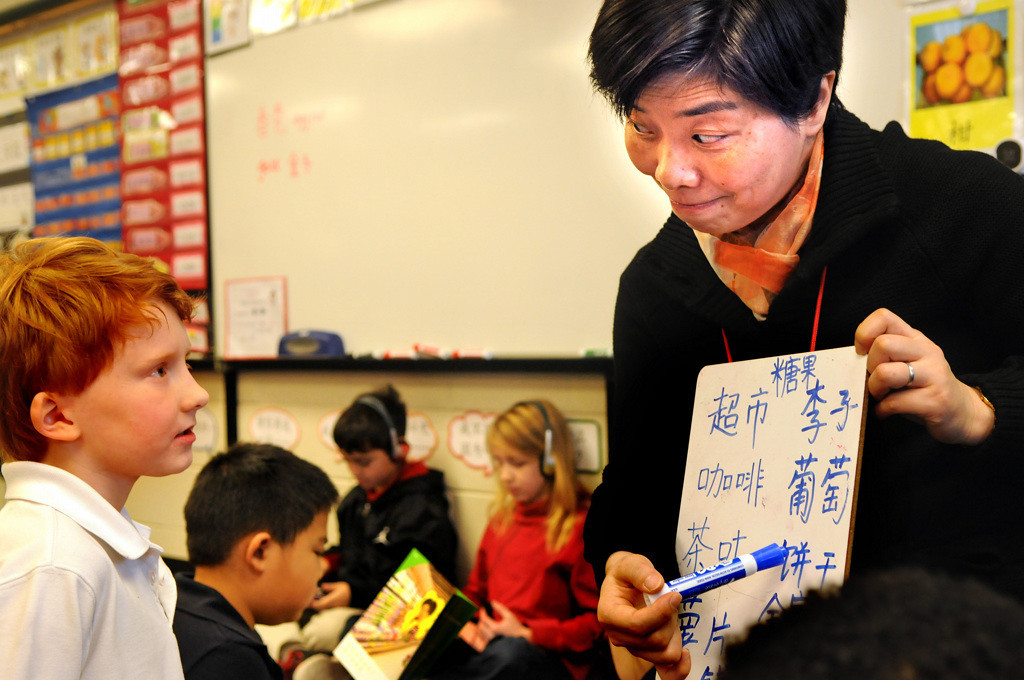 . Second-grade teacher Ping Chen, right, helps Finnegan Black learn Chinese words found in a book he is reading for a Chinese Immersion class at Hamline Elementary in St. Paul on Wednesday, Jan. 22, 2014. The school has seen many changes under the school district\'s \'Strong Schools, Strong Communities \' plan -- among them the addition of the Chinese Immersion program. (Pioneer Press: Jean Pieri)