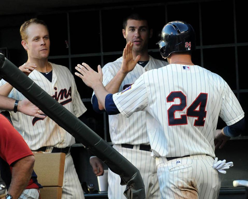 . Minnesota Twins Justin Moreau, back left, and Joe Mauer congratulate Trevor Plouffe in the sixth inning. (Pioneer Press: Sherri LaRose-Chiglo)