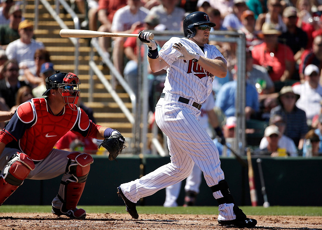 . Minnesota Twins\' Chris Parmelee, right, follows through on a swing as Boston Red Sox catcher A.J. Pierzynski, left, looks on in the first inning of an exhibition baseball game, Saturday, March 1, 2014, in Fort Myers, Fla. Parmelee hit a three-run homer in the sixth inning to help the Twins beat the Red Sox 6-2. (AP Photo/Steven Senne)