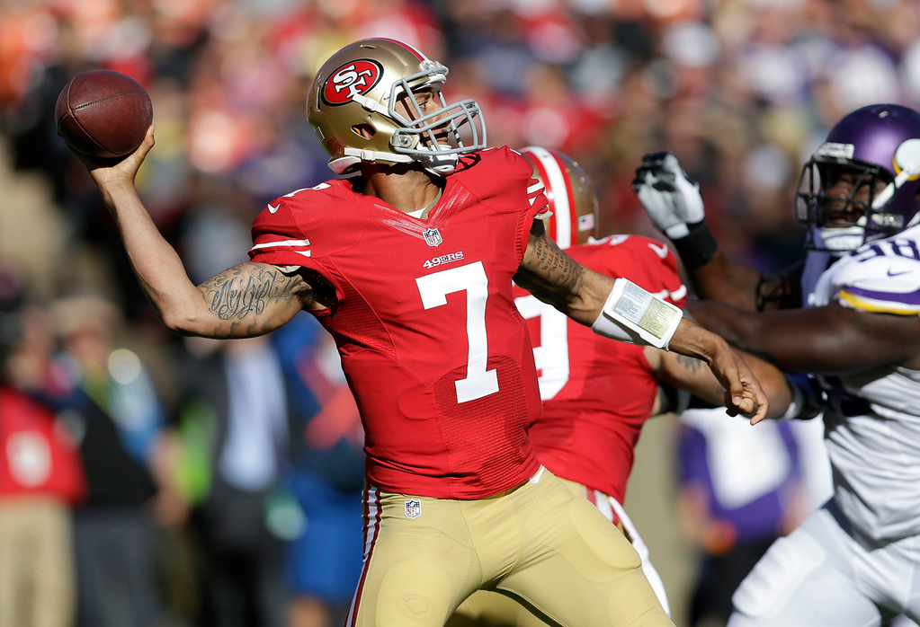 . 49ers quarterback Colin Kaepernick  passes while under pressure from Vikings defensive tackle Letroy Guion during the first quarter. (AP Photo/Marcio Jose Sanchez)