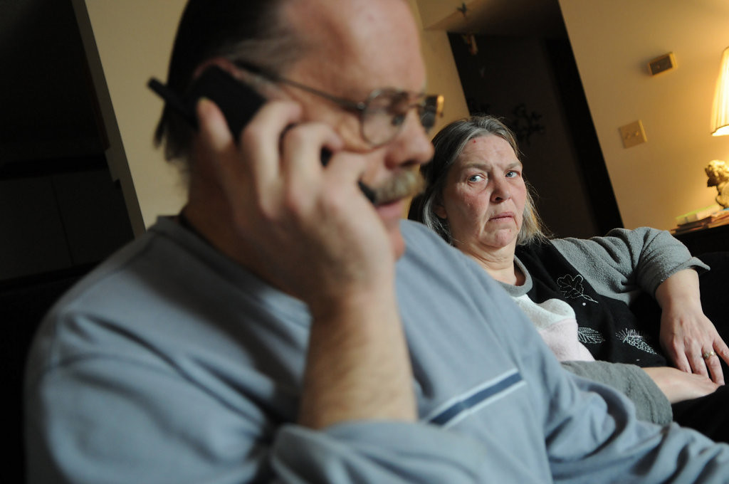 . Linda Milligan, right, listens as her husband, Ron Milligan, answers questions from a state of Minnesota employee regarding his canceled health insurance. (Pioneer Press: Jean Pieri)
