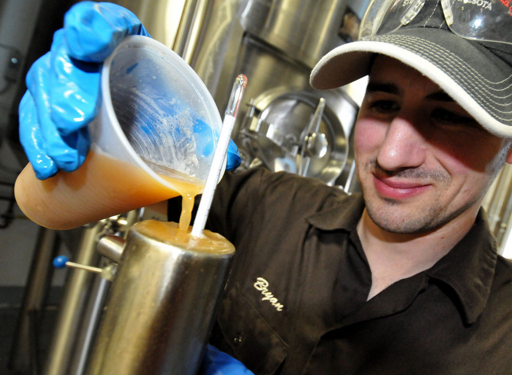 . Assistant brewer Bryan Trost takes a density reading of the developing beer at the Lift Bridge Brewery. (Pioneer Press: John Doman)