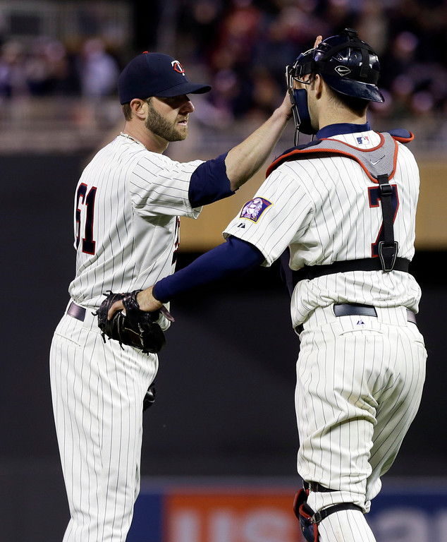 . Minnesota Twins catcher Joe Mauer, right, congratulates pitcher Jared Burton who picked up the save as they defeated the Baltimore Orioles 8-5 in a baseball game on Saturday, May 11, 2013, in Minneapolis. (AP Photo/Jim Mone)