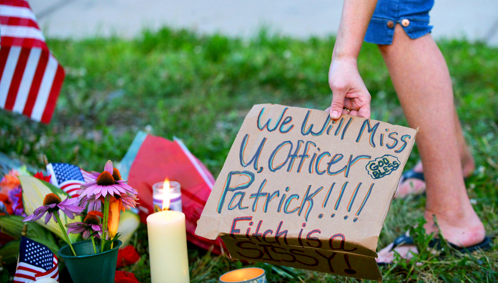 . A mourner lays a sign remembering Mendota Heights police officer Scott Patrick during a candle light vigil. Officer Patrick was killed by a suspect while performing a traffic stop on Dodd Road in just over the West St. Paul border, near Smith Avenue on Wednesday, July  30, 2014. (Pioneer Press: John Autey)