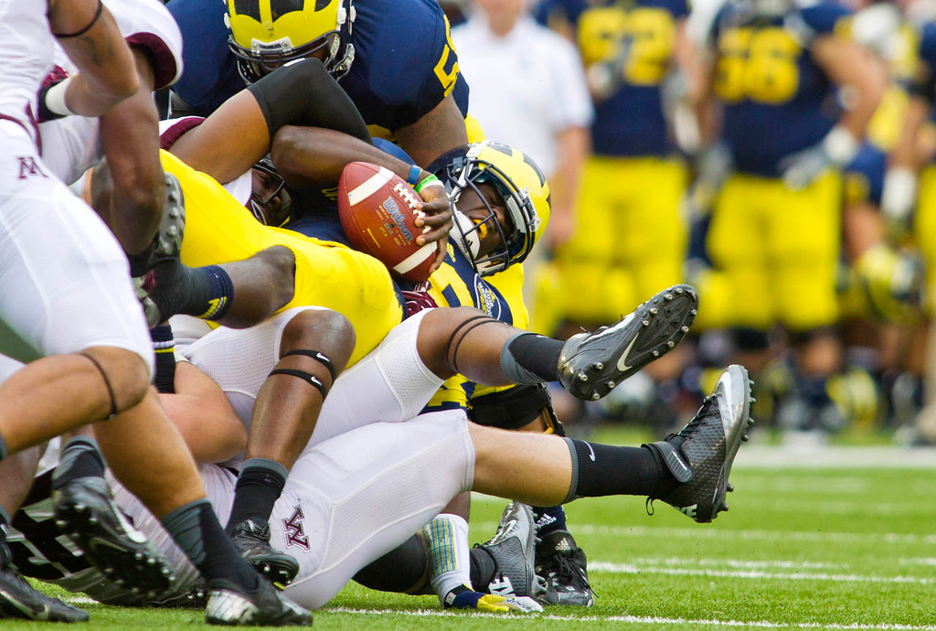 . Michigan quarterback Devin Gardner, center, is sacked by Minnesota in the second quarter. (AP Photo/Tony Ding)