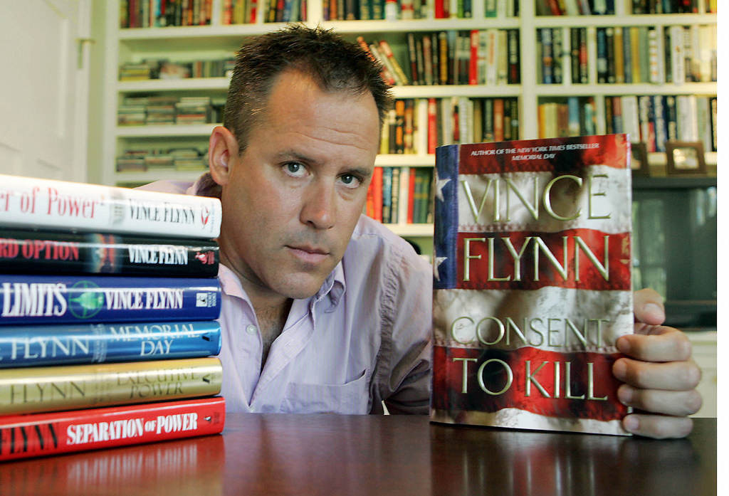 """. Flynn shows the dust jacket of his new book, \""""Consent to Kill,\"""" along with copies of  his six earlier books, at his home in Edina in 2005. He credited his sales experience with Kraft General Foods with helping him learn how to promote his first  book at bookstores. (Associated Press: Jim Mone)"""