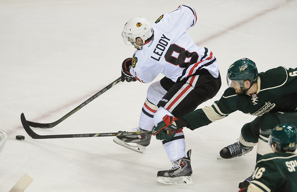. Minnesota defenseman Marco Scandella reaches to try and get the puck from Chicago defenseman Nick Leddy in the second period.  (Pioneer Press: Ben Garvin)