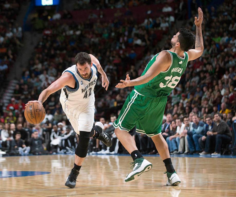 . Minnesota Timberwolves\' Kevin Love, left, drives to the net as Boston Celtics\' Vitor Faverani defends during the third quarter. (AP Photo/The Canadian Press, Graham Hughes)