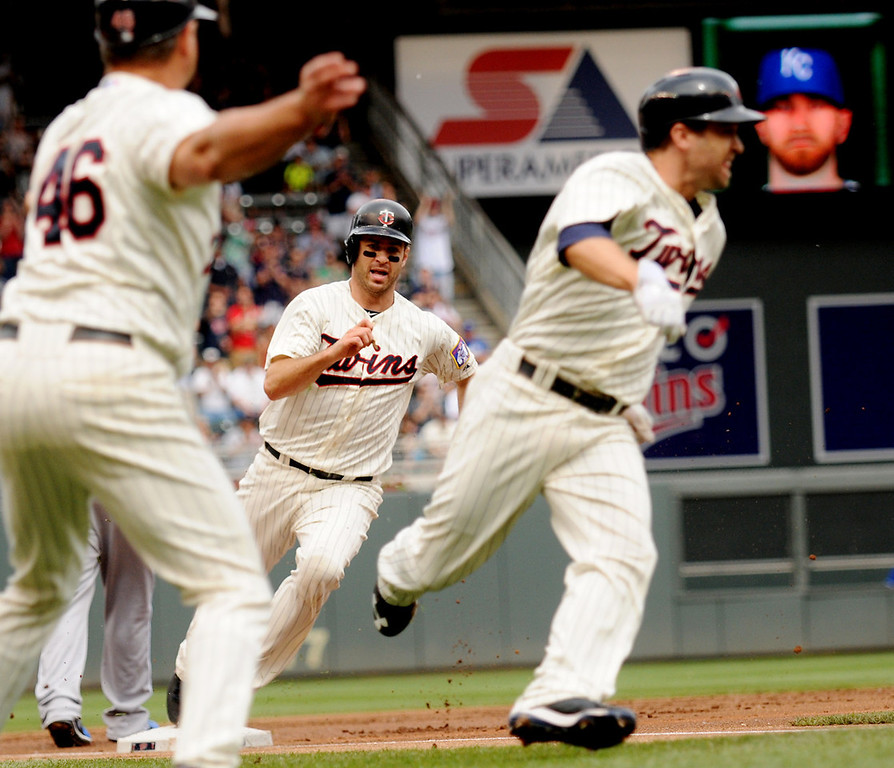 . Minnesota third base coach Joe Vavra waves Brian Dozier, right foreground, and Joe Mauer home as both round third to score on a Justin Morneau double in the first inning. (Pioneer Press: John Autey)