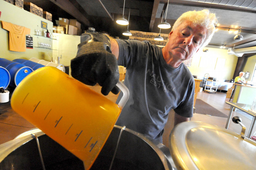 . Peter Thurgood places malt into the brewing kettle as he brews a batch of his 100% Evil India Pale Ale at Vine Park Brewery.  (Pioneer Press: John Doman)