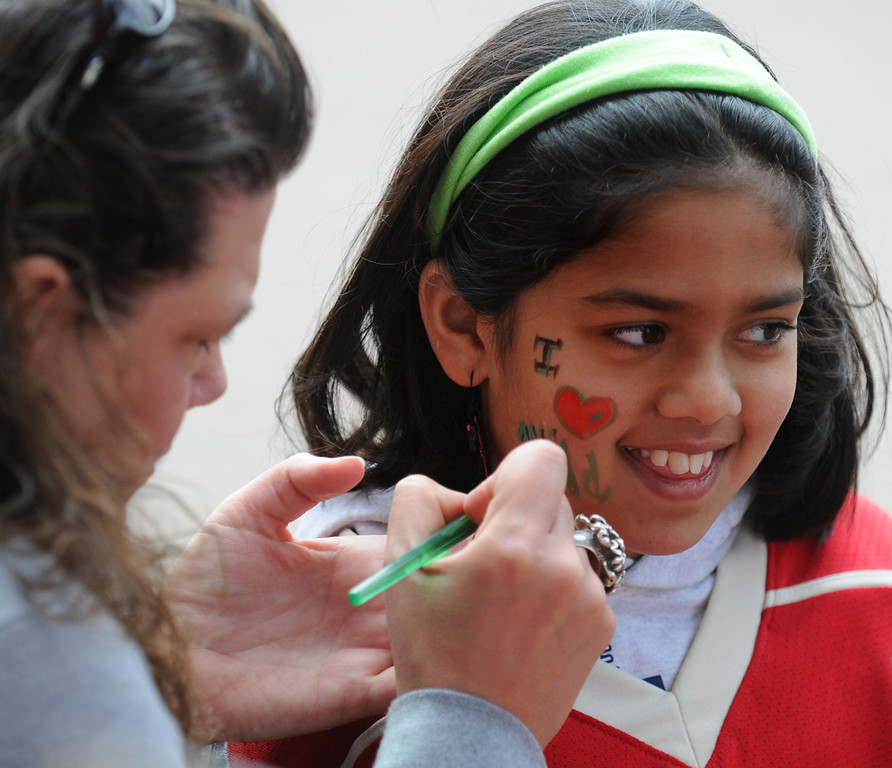 ". Nine-year-old Rithima Chittajallu of Eagan, right gets an  ""I (heart) Wild\"" from artist Darcy Young before the start of Game 3 against the Blackhawks. (Pioneer Press: John Autey)"