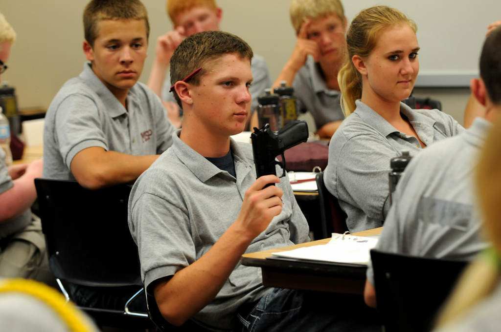 . Isaac Holm of Faribault holds an unloaded gun before passing it to another cadet as a state trooper instructs the cadets on different guns and has them pass them around the class.  (Pioneer Press: Jean Pieri)