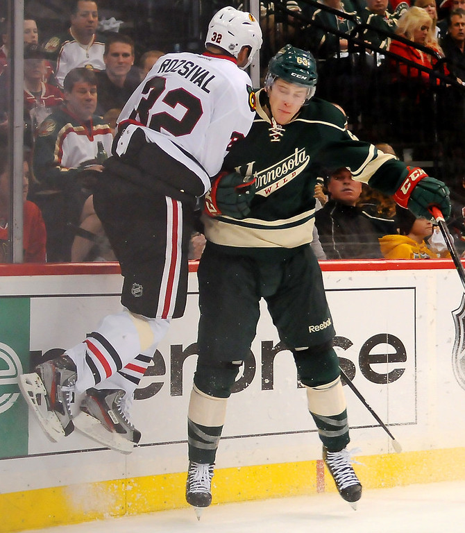 . Minnesota right wing Charlie Coyle, right, checks Chicago defenseman Michal Rozsival off his skates and into the glass behind the Chicago net in the second period. (Pioneer Press: John Autey)
