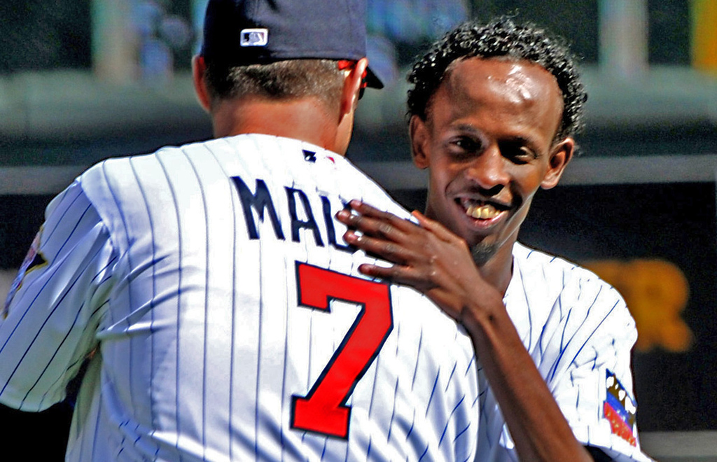 """. Barkad Abdi, star of the movie \""""Captain Phillips,\"""" hugs Twins first baseman Joe Mauer after Abdi threw out the ceremonial first pitch. (Pioneer Press: John Autey)"""