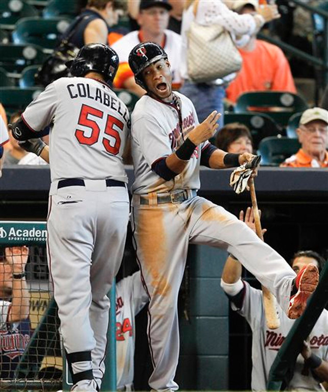 . Minnesota Twins\' Chris Colabello  celebrates with Pedro Florimon  after hitting a grand slam home run against the Houston Astros in the ninth inning. The Twins won 10-6. (AP Photo/Bob Levey)