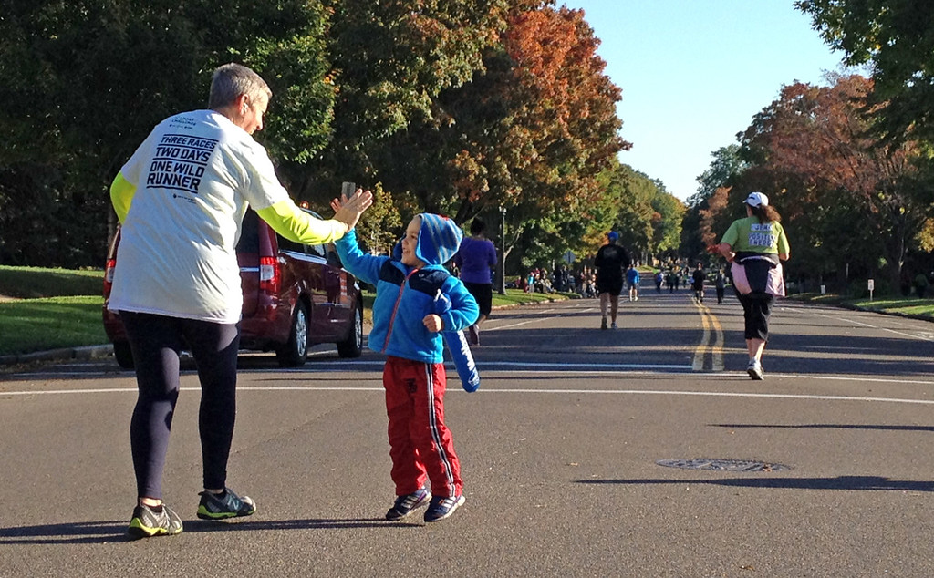 . Four-year-old Landen Knox of Minneapolis supplied Twin Cities Marathon runners with high-fives along Summit Avenue in St. Paul while waiting for his mom to pass. (Pioneer Press: John Brewer)