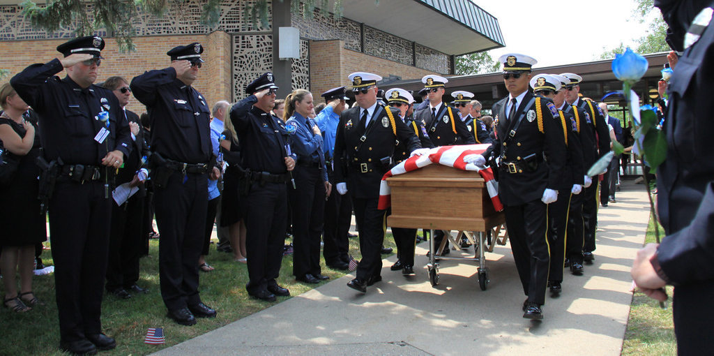 . Police officers salute as the coffin of Mendota Heights police officer Scott Patrick is carried from St. Stephen\'s Lutheran Church in West St. Paul after funeral services on Wednesday.  (Minnesota Department of Public Safety Pool Photo: Jen Longaecker)