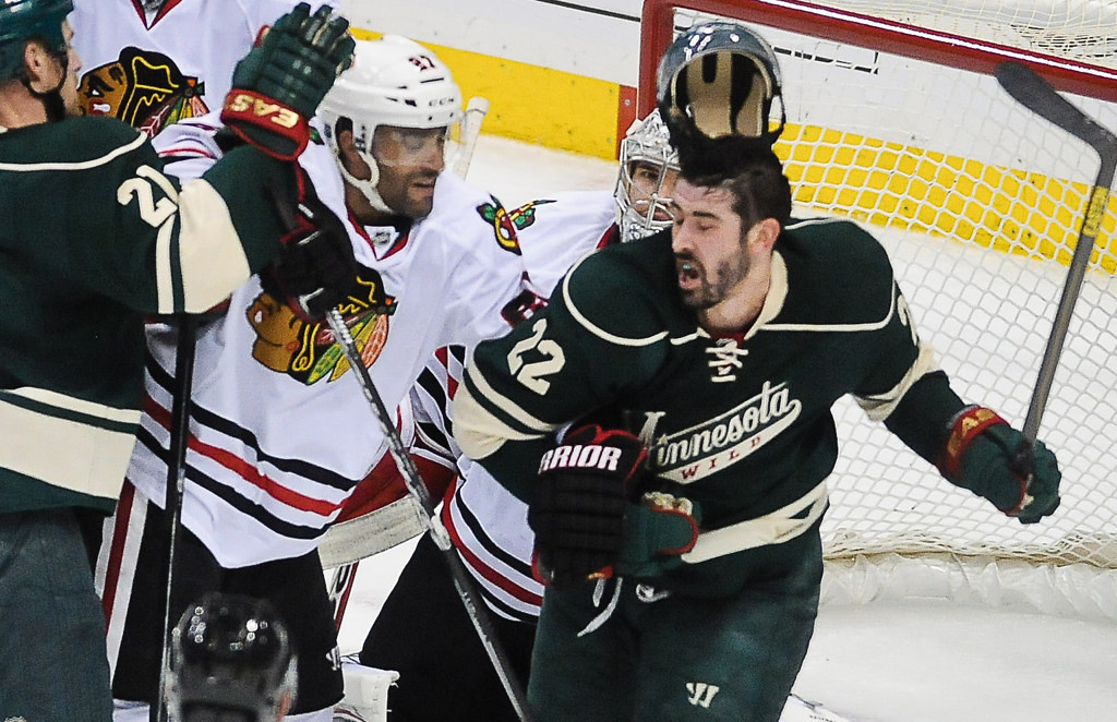 . Minnesota\'s Cal Clutterbuck, right, has his helmet knocked off by Chicago defenseman Johnny Oduya, center, during a second period tussle. At left is Kyle Brodziak.   (Pioneer Press: Ben Garvin)