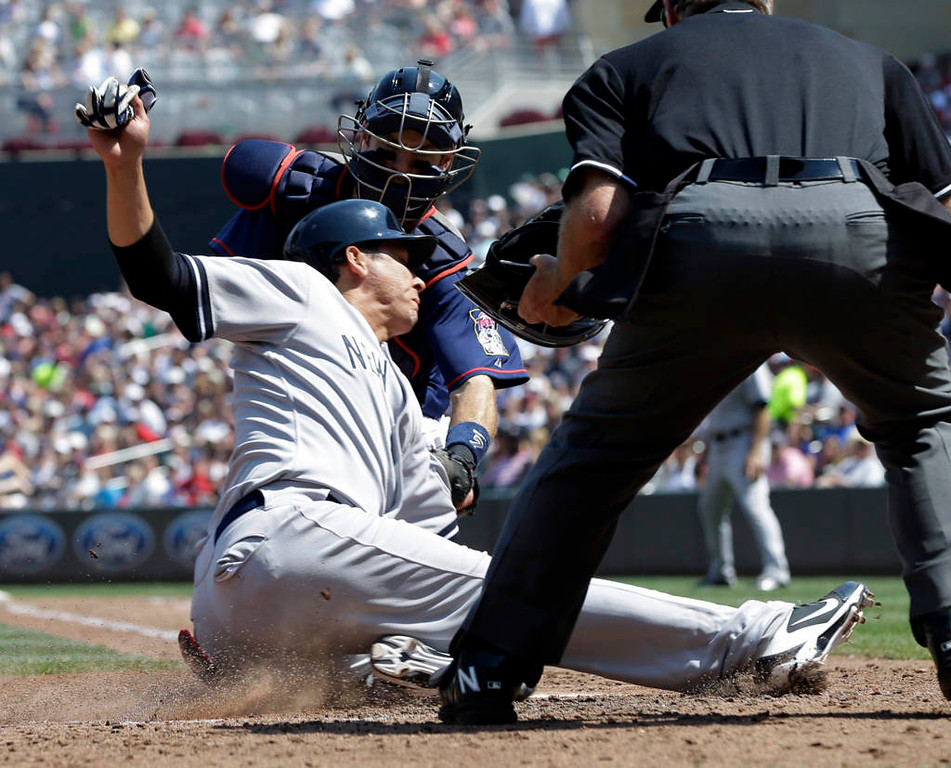 . New York\'s Luis Cruz, left, slides into the tag by Minnesota catcher Joe Mauer and is out in the sixth inning. (AP Photo/Jim Mone)