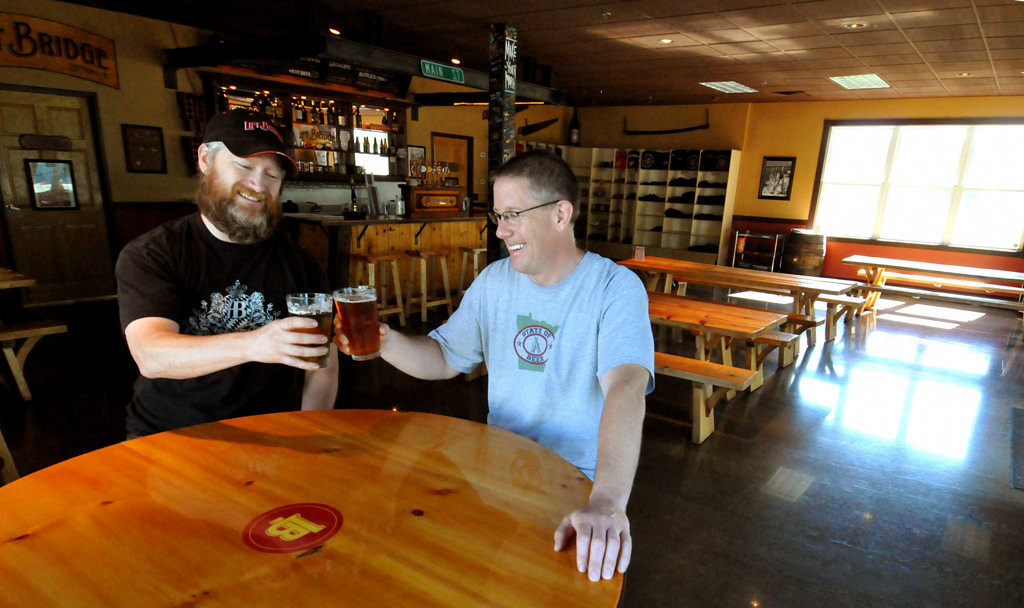 . Brewmaster Matt Hall, left, and co-owner and vice president for finance Jim Pierson toast each other in the tasting room at Lift Bridge Brewery. (Pioneer Press: John Doman)