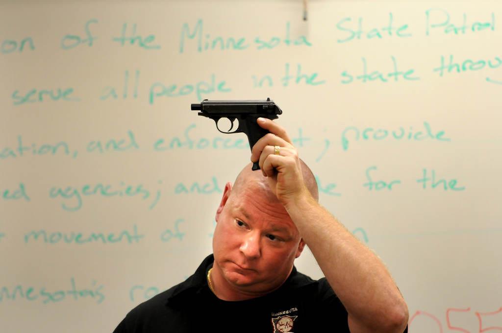 . Minnesota State Patrol Sgt. Jason Halvorson describes a Browning .22 to students. (Pioneer Press: Jean Pieri)