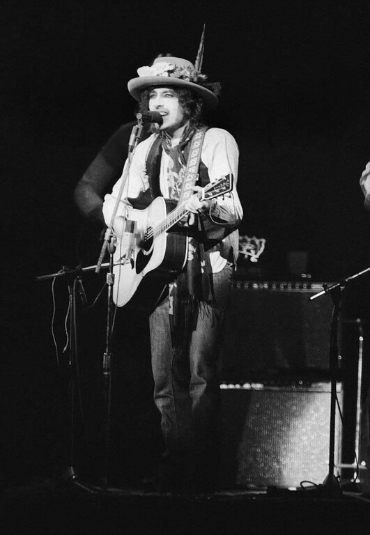 """. Bob Dylan performs before a sold-out crowd of about 20,000 in New York\'s Madison Square Garden, Dec. 8. 1975 at a benefit concert to support efforts to get a new trail for former Boxer Rubin \""""Hurricane\"""" Carter.  Carter is now serving three-life sentences for murder in New Jersey.  (AP Photo/Ray Stubblebine)"""