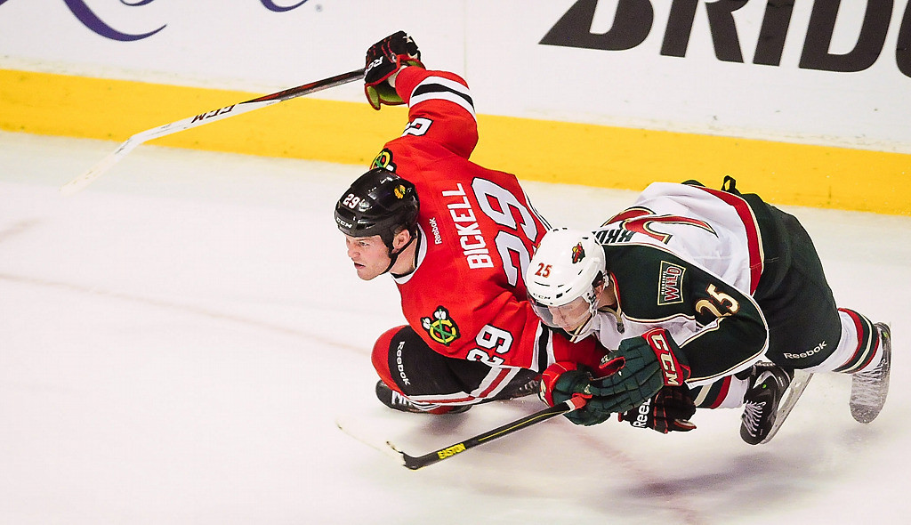 . Chicago Blackhawks left wing Bryan Bickell  falls to the ice after making a long empty-net goal under pressure from Minnesota Wild defenseman Jonas Brodin. (Pioneer Press: Ben Garvin)