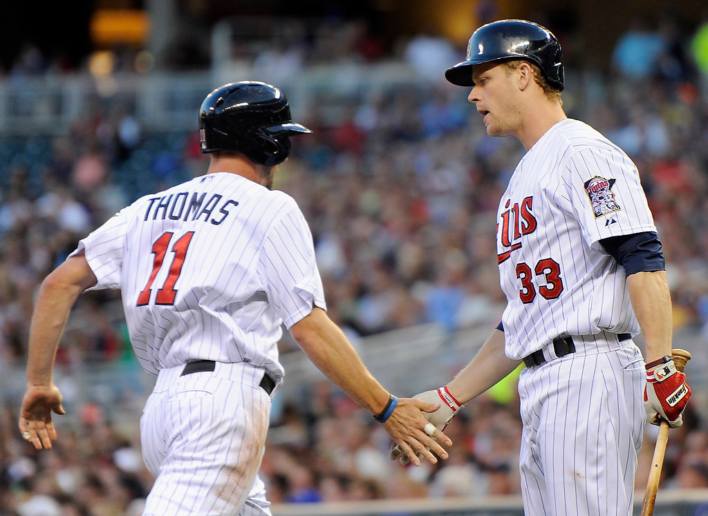 . Justin Morneau congratulates teammate Clete Thomas on scoring a run against the Houston Astros during the third inning.  (Photo by Hannah Foslien/Getty Images)