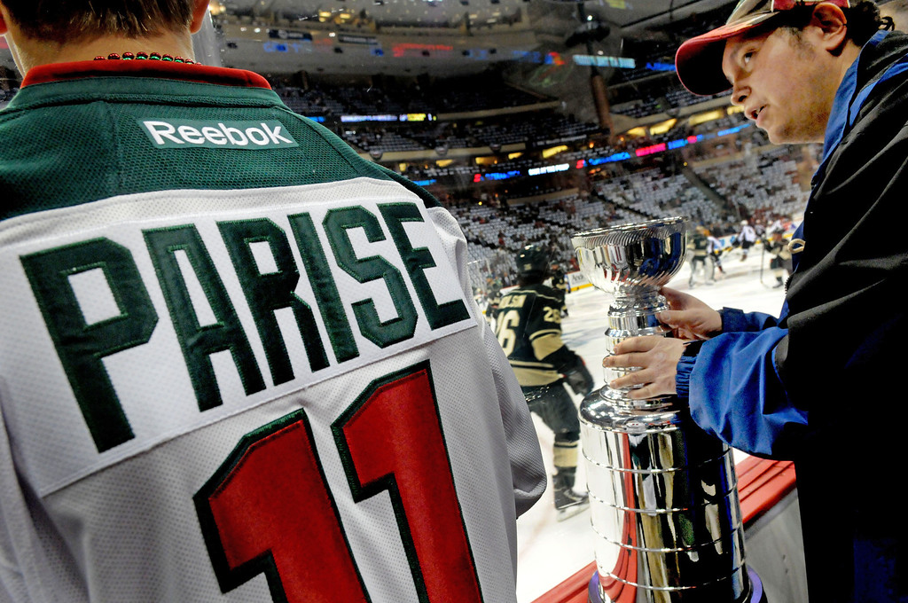 . Steve Cassidy of Bloomington, right, watches the Minnesota Wild players skate during warmups alongside his miniature Stanley Cup with pal Billy Riviere of Medina. (Pioneer Press: Sherri LaRose-Chiglo)