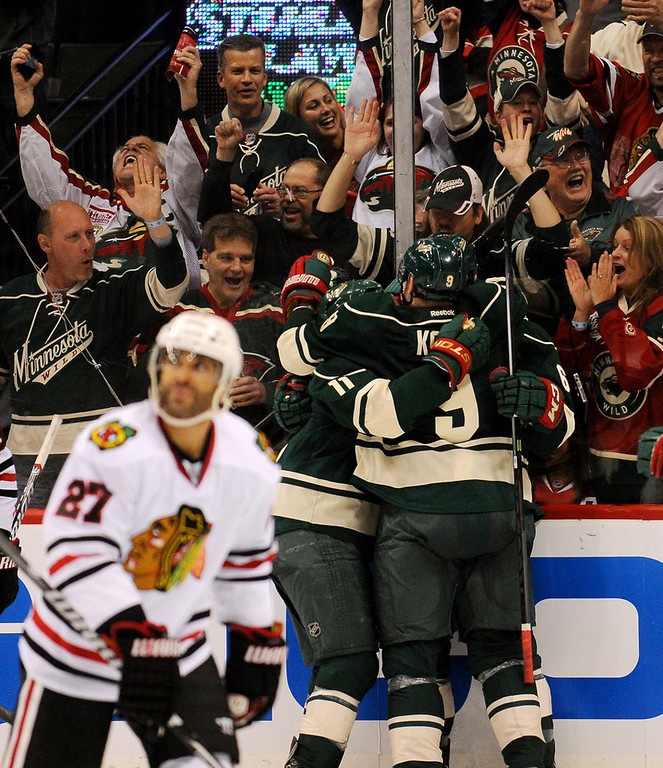 . Wild teammates celebrate Zach Parise\'s game-tying goal in the third period as Chicago defenseman Johnny Oduya, left, skates away.  (Pioneer Press: John Autey)
