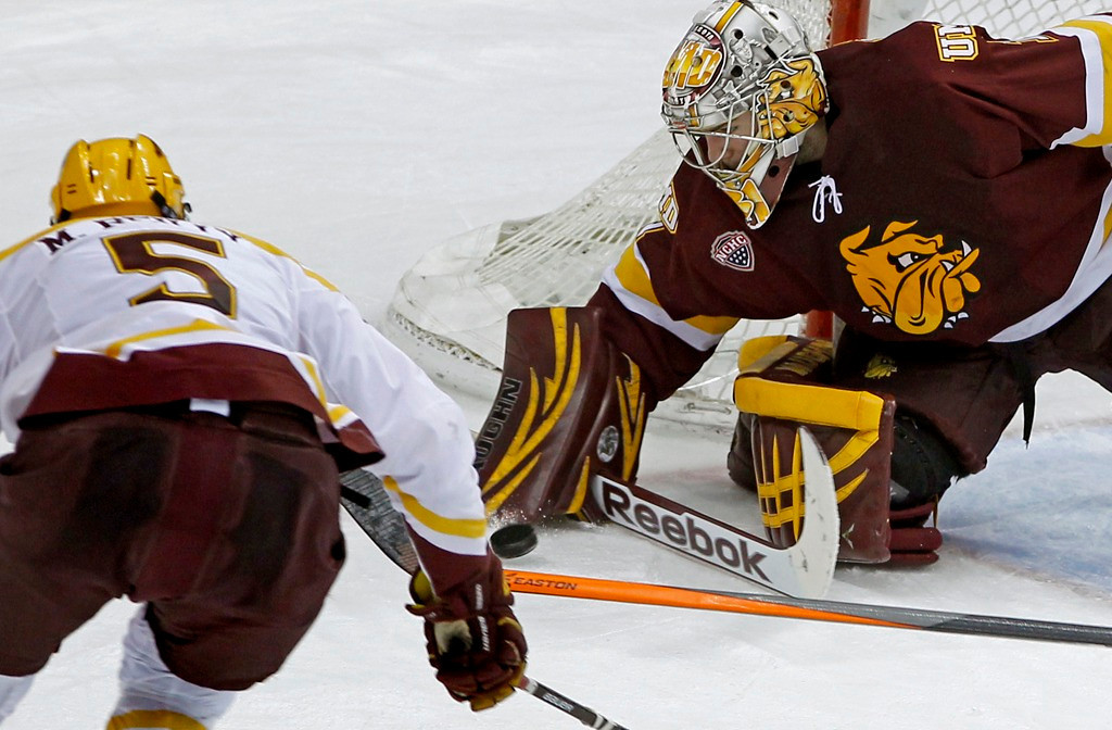 . Minnesota Duluth goalie Aaron Crandall, right, blocks a shot by Gophers defenseman Mike Reilly during the second period. (AP Photo/Ann Heisenfelt)