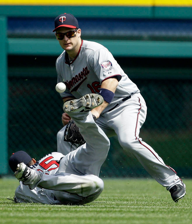 . Minnesota Twins left fielder Josh Willingham, top, reaches in to secure the ball as shortstop Pedro Florimon misplays the single hit by Detroit Tigers\' Alex Avila during the sixth inning of a baseball game in Detroit, Sunday, May 26, 2013. (AP Photo/Carlos Osorio)