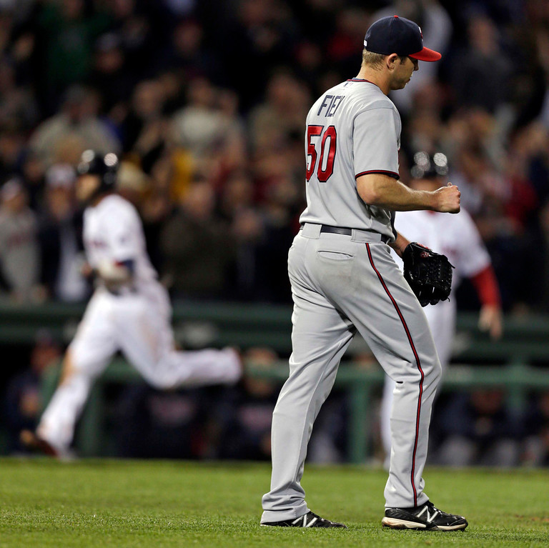 . Minnesota Twins relief pitcher Casey Fien walks back to the mound with a fresh baseball as Boston Red Sox\'s Dustin Pedroia rounds the bases on his solo home run during the eighth inning. (AP Photo/Charles Krupa)